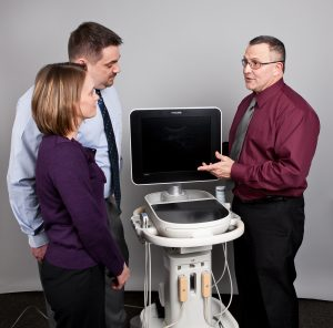 Dr. Andersen showing ultrasound machine to patients.
